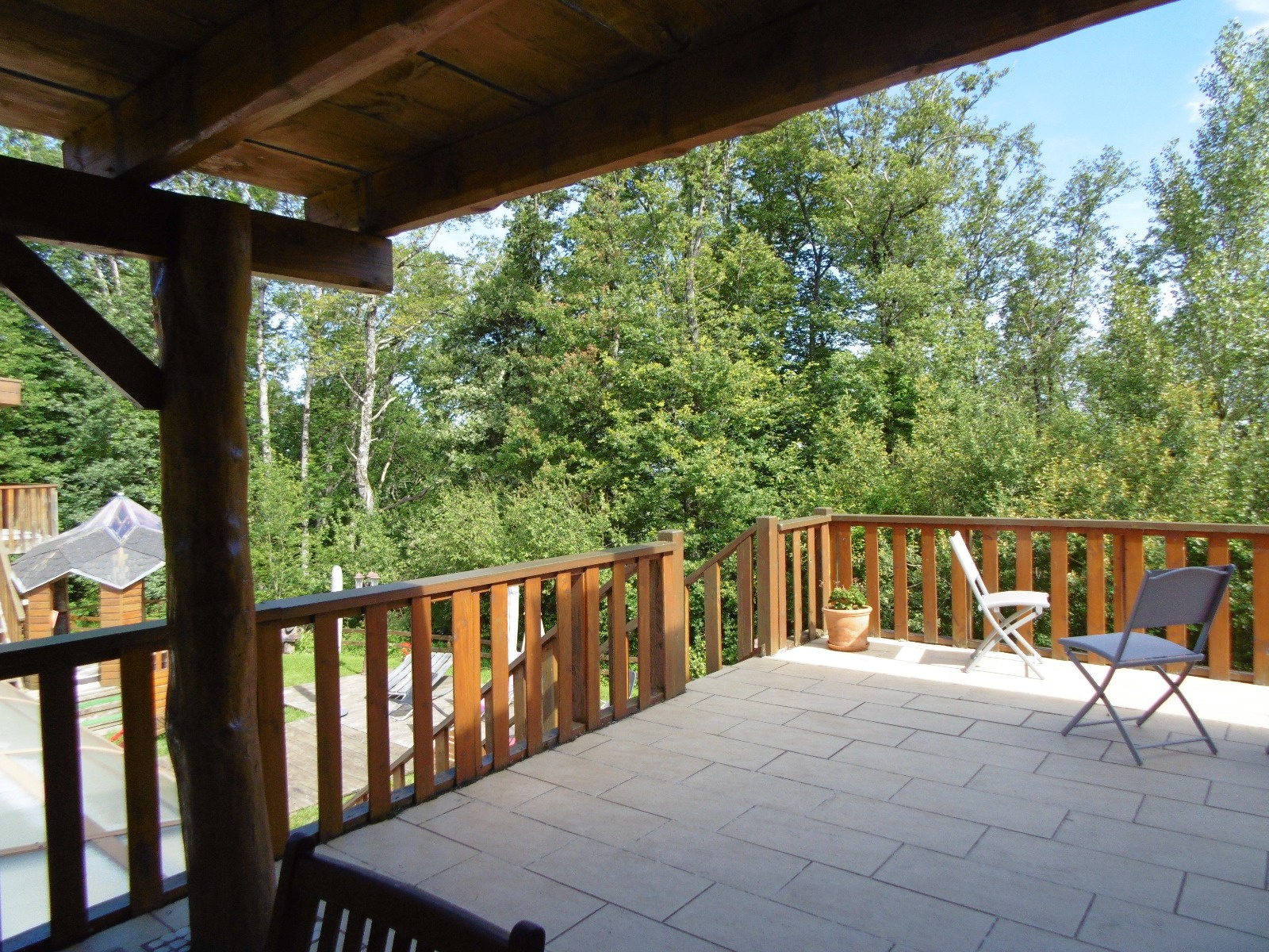 Terrasse couverte prolongeant l'espace tables d'hôtes